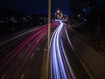 Traffico che si stria giù una strada principale alla notte Immagini Stock
