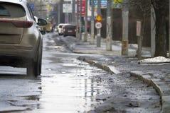 Traffico cittadino durante il disgelo della molla Strada con le pozze Fotografia Stock Libera da Diritti