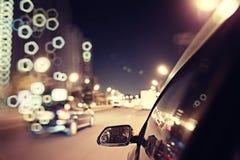 Traffico degli ingorghi stradali di notte della sfuocatura del fondo Fotografia Stock