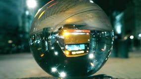Traffico della via della città di notte che riflette sottosopra nella palla di vetro immagini stock