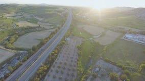 Traffico occupato sulla strada Colpo aereo della terra con attenzione coltivata di azienda agricola, giardini stock footage