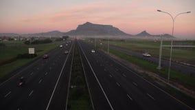 Traffico stradale a Cape Town, con la montagna della Tabella nei precedenti, nelle prime ore del mattino video d archivio