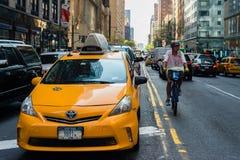 Traffico, taxi e ciclista in NYC immagini stock