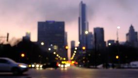 Traffico vago nella città alla notte Automobili che si muovono attraverso un'intersezione con gli edifici di Chicago nei preceden archivi video