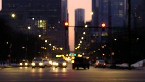 Traffico vago nella città alla notte Automobili che si muovono attraverso un'intersezione con gli edifici di Chicago nei preceden stock footage