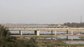 Trafic automobile sur le pont à hauteurs Signature sur la rivière Yamuna à Delhi, en arrière-plan de la ville banque de vidéos