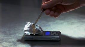 Traficante de drogas que pesa uma droga em uma escala digital vídeos de arquivo