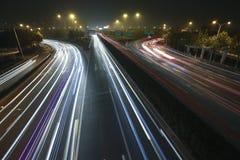 Trafik för natt för ljus för regnbåge för siktsskymning stads- på huvudvägen Royaltyfria Bilder