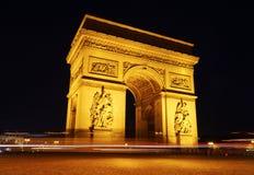 Trafik går runt om Arc de Triomphe på natten Royaltyfria Bilder