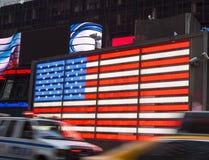 Trafik i Times Square framme av amerikanska flaggan Arkivbild