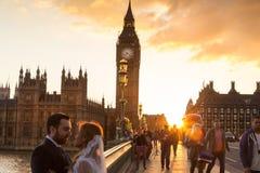 Trafik och slumpmässigt folk på den Westminster bron i solnedgång, London, UK Royaltyfri Foto