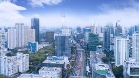 Trafik på den upptagna vägen med höga byggnader arkivbilder