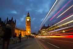 Trafik på den Westminster bron på skymning Arkivfoton
