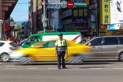 Trafik Warden Directs Peak Hour Traffic i Tapei Fotografering för Bildbyråer