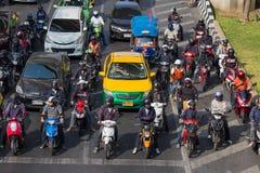 Trafikera flyttningar långsamt längs en upptagen väg i Bangkok, Thailand Arkivbilder