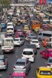 Trafikera flyttningar långsamt längs en upptagen väg i Bangkok, Thailand Royaltyfri Bild