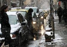 Trafikera på gatan i snöfall i dystert väder, blodstockning av bilar, trafikstockning med ljus royaltyfri foto