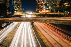 Trafikera på motorvägen 110 och byggnaderna i Los Angeles på natten Arkivfoto