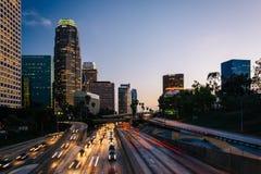 Trafikera på motorvägen 110 och den Los Angeles horisonten på solnedgången Arkivfoto