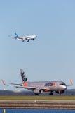 Trafikflygplan för Jetstar Airways flygbuss A320 på Sydney Airport med Kina en sydlig flygbuss A330 på inställning i bakgrunden Fotografering för Bildbyråer