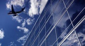 Trafikflygplan som flyger över höga kontorsbyggnader Royaltyfria Bilder