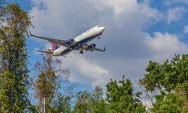 Trafikflygplan som landar låga near träd Royaltyfria Bilder