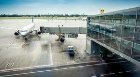 Trafikflygplan som parkeras bredvid logiporten i flygplatsterminal Arkivfoto