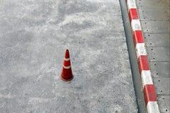 Trafikkottar, cementbottenvåningen och plast- band för röda kottar för trafik vita och är säkerhetsutrustning på vägen arkivfoton