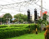 Trafiklampljus för drevpendlarelinje med trädet och elektrisk kabel för gräsplanbuske i bogor indonesia Royaltyfri Bild