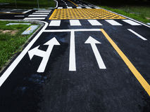 Trafiklinje och tecken på asfalt Arkivfoto