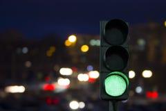 Trafikljus - grön signal på natten på de tillbaka ljusen av bilar royaltyfri bild