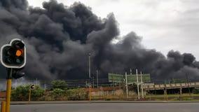 Trafikljus i stad med svart giftlig rök i bakgrunden arkivfoton