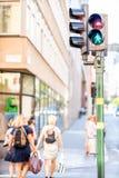 Trafikljus med det fot- tecknet och kvinnor som korsar en gata Fotografering för Bildbyråer