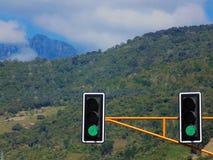 Trafikljus med klartecken som är främst av bergen fotografering för bildbyråer