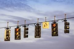 Trafikljus som hänger ovanför gatan Arkivbild