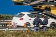 Trafikpolisen att kontrollera hastigheten av medel på sidan av huvudvägen med en hastighetskamera royaltyfria bilder