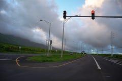 Trafiksignal på uppdelningen av vägen med molnig himmel Arkivbild