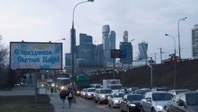 Trafikstockning mot bakgrunden av en affischtavla och en skyskrapaMoskvastad arkivfilmer