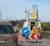 Trafiktecken av reparationen och arbetaren Detouring vägreparation för bilar Arkivbild