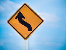Trafiktecken för kurvor framåt på blå himmel Royaltyfri Fotografi