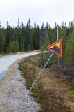 Trafiktecken som varnar om hög löneförhöjning på en curvy väg Arkivbild