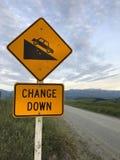 Trafiktecken: Tecken för brant nedstigning på gul bakgrund Vägen stiger ned Varningstecknet lät dig veta vägändringar är kommande royaltyfri fotografi