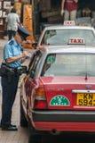 Trafikvakten skriver upp en bil för brott på Hong Kong Island China arkivbilder