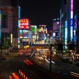 Trafique córregos no distrito de Shinjuku na noite no Tóquio, Japão Foto de Stock Royalty Free
