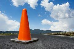 Trafique el cono en un camino con un cielo azul brillante Imagen de archivo