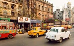 Trafique en el camino indio con los mercados y los coches antiguos del embajador que apresuran Foto de archivo libre de regalías