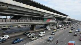 Trafique a estrada perto da linha roxa do MRT na estação de Pai do golpe em Nonthaburi, Tailândia filme