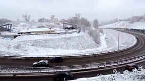 Trafique la conducción a lo largo del camino de ciudad durante tormenta intensa de la nieve metrajes