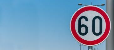 Trafique o sinal do limite de velocidade para a limitação em 60 quilômetros ou quilômetros por hora com fundo do céu azul com esp Imagem de Stock Royalty Free