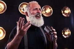 Trafnie spojrzenie emocjonalny szary brodaty mężczyzna śpiew w srebrze Obraz Stock